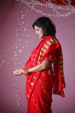 Side view of pregnant Indian lady holding oil lamp Stock Photo