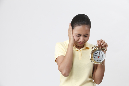 Malay woman holding an alarm clock.