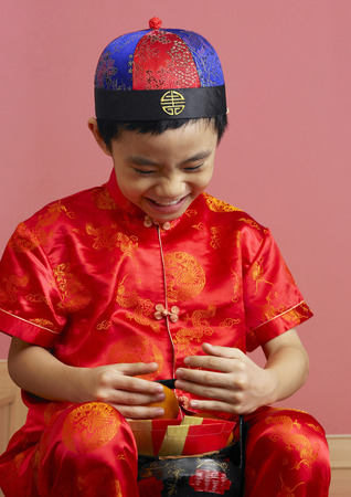 A boy laughing happily for having so many mandarin oranges and angpao with him