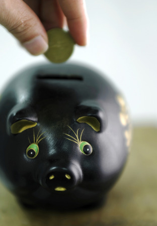 Inserting coin into a piggy bank