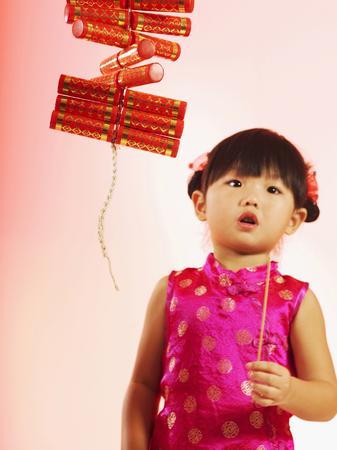 A girl in a daze holding a joss stick Foto de archivo
