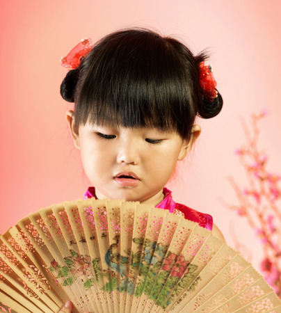 A girl looking at a wooden made fan