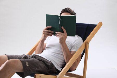 man sitting on beach chair  reading book Stock fotó