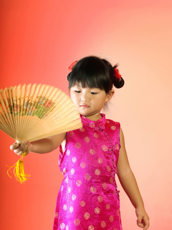 A girl holding a wooden made fan Archivio Fotografico