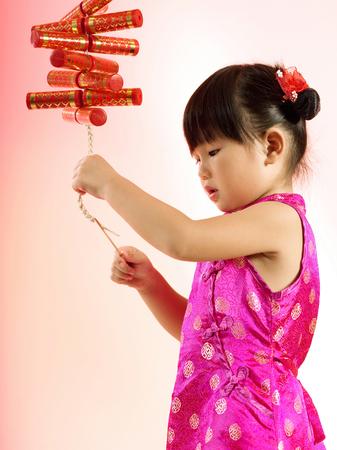 Una niña encendiendo un fuego artificial.