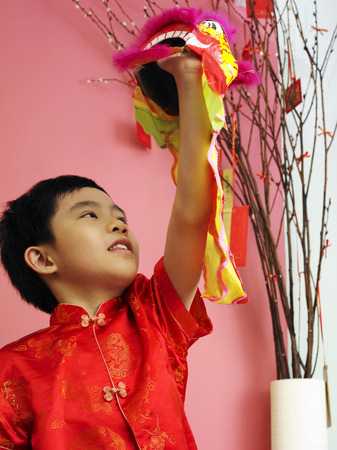 A boy raising his lion dance toy Imagens