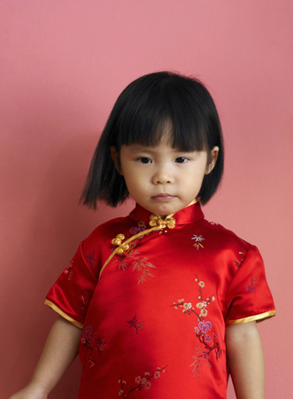 A girl in cheongsam standing in front of the camera