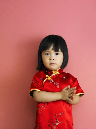 A girl in cheongsam giving people chinese new year wishes