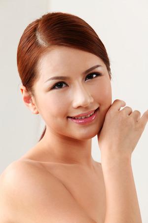Mujer tocando su rostro sobre el fondo blanco. Foto de archivo