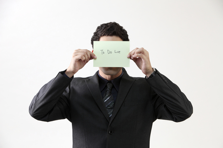 Businessman holding message card,covered his face Imagens