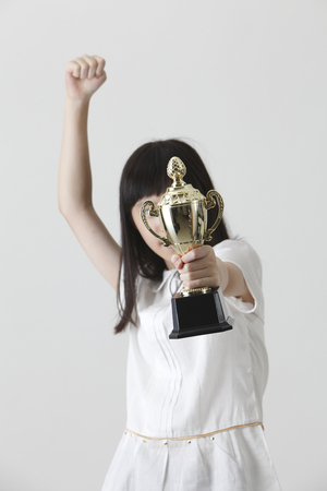 chinese girl holding trophy covered her face