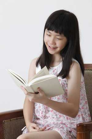 chinese girl sitting on the sofa reading book with smile Banco de Imagens - 121497196