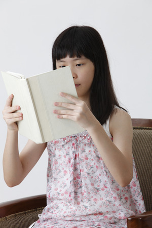 chinese girl sitting on the sofa reading book Banco de Imagens - 121497166