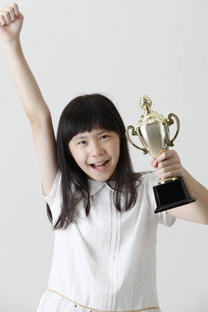 chinese girl holding trophy with raising her arm