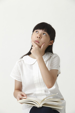 chinese girl holding avcover book looking up