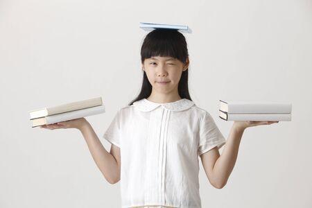 Chinese girl balancing books 免版税图像