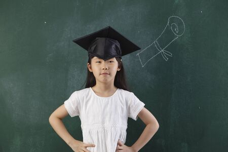 chinese girl with the mortarboard in front of blackboard
