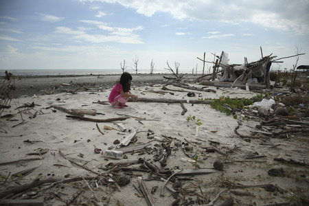 child playing at the polluted beach Imagens
