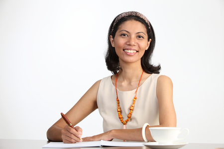 malay woman hold a pen sitting at office desk