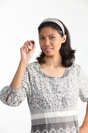malay woman holding a marker pen looking at camera