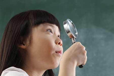 close up of child holding a magnifier