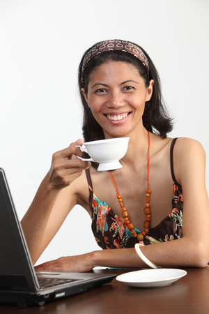 Malay woman holding a tea cup in front of the laptop Imagens