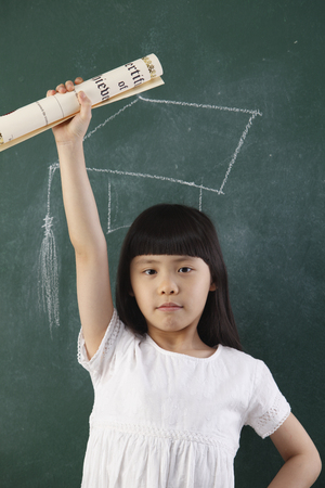 girl holding certificate in front of blackboard Imagens