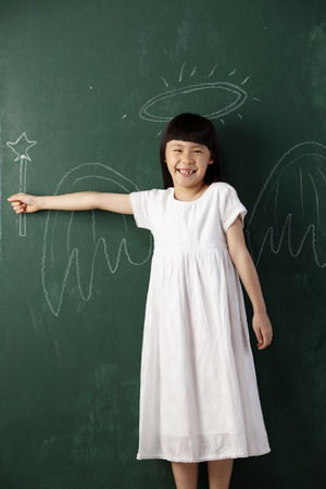 cute litte angel in front of black board
