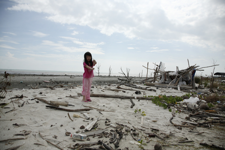 child playing at the polluted beach 版權商用圖片