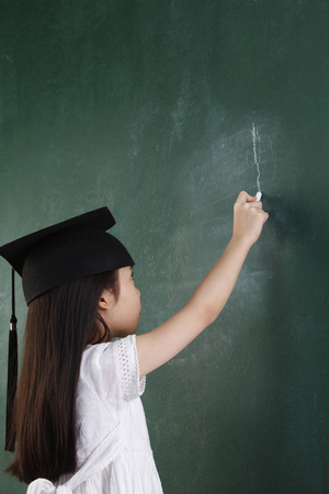 girl with the mortar board writting with chalk Imagens