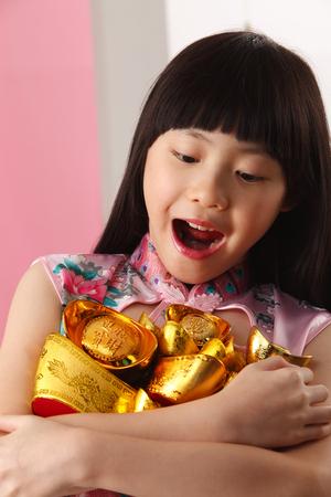 little girl holding bunch on ingot looking down Imagens