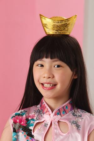 girl balance golden ingot on her head