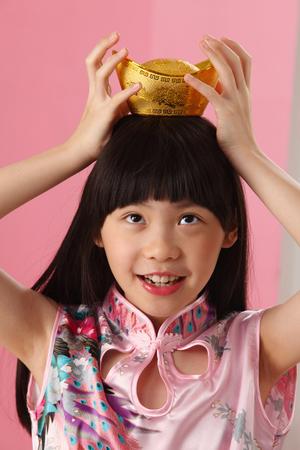 girl putting ingot on her head balancing