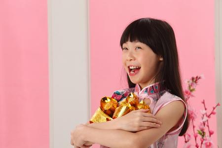 little girl holding bunch on ingot Banco de Imagens