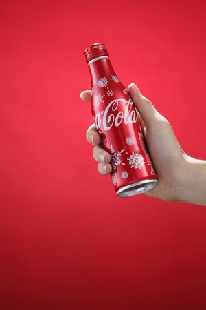 Kuala Lumpur,Malaysia 11th July 2016, Hand hold a bottle christmas edition of Coca-Cola on red background. Coca Cola drinks are produced and manufactured by The Coca-Cola Company.