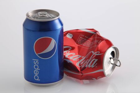 Kuala Lumpur,Malaysia.Jan 6, 2016 Photo of a Coca-Cola and Pepsi classic cans. Concept of competitiveness as Coca-Cola can is lying empty and crashed while Pepsi is still full and standing. Redakční