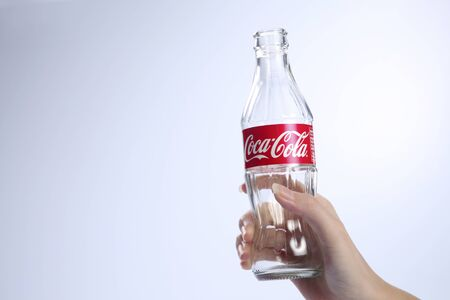 kuala lumpur-malaysia, 16th november 2015, female hand holding  empty  coca cola glass bottle