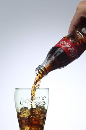 KUALA LUMPUR, MALAYSIA - Feb 17, 2016 pouring coca cola to a glass with ice cube Редакционное