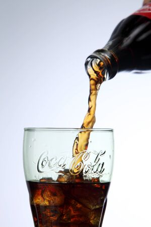 KUALA LUMPUR, MALAYSIA - Feb 17, 2016 pouring coca cola to a glass with ice cube Editorial