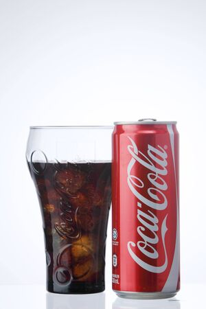 KUALA LUMPUR, MALAYSIA - Feb 17, 2016  Can of coca cola and glass with ice cube on the white background