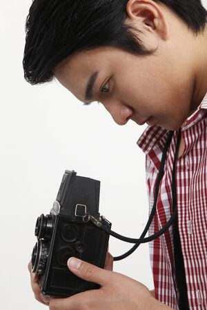 side view of man holding antique camera