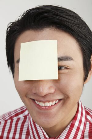 man with an adhesive note on his forehead