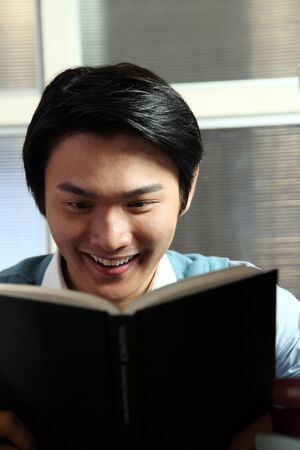 Young man reading by piled books,