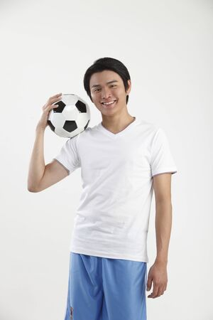 teenage holding football on the shoulder