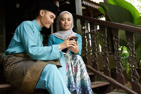 Muslim couple in traditional Malay clothing sitting at wooden stair using smart phone during Eid al-Fitr celebration. Stock fotó