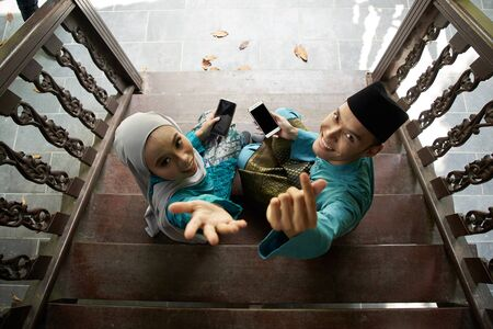 top view of Muslim couple in traditional Malay clothing sitting at wooden stair using smart phone during Eid al-Fitr celebration. Stock fotó