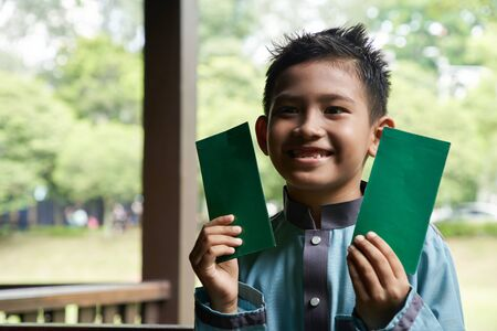 malay boy in a Malay traditional costume showing his happy face after receiving money pocket during Hari Raya celebration
