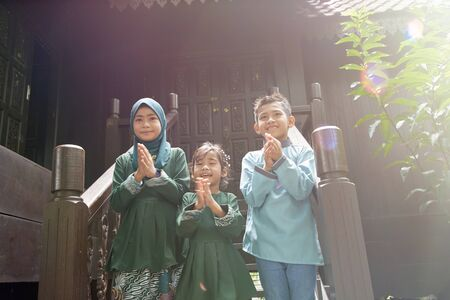Malay family in Malay traditional showing their happy reaction during Hari Raya celebration.
