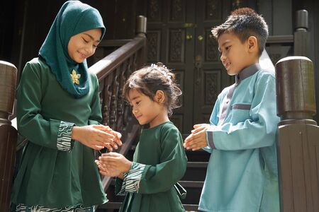 kids in traditional clothing , greeting in front of traditional malay house  during Hari Raya celebration.