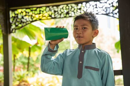 Malay boy with traditional clothing showing his happy reaction after received money pocket during Eid Fitri or Hari Raya celebration